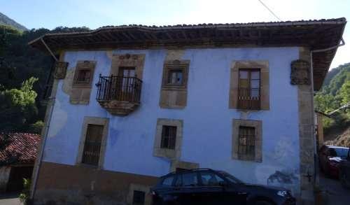 15 Une maison de maître au balcon original en fer forgé savamment travaillé se distingue du bâti général de fermes